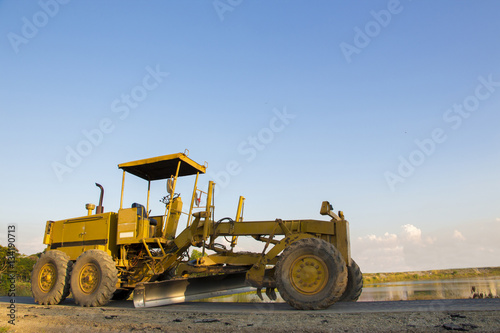 Poster A huge yellow road grader parked on a roadside with clear blue sky as background