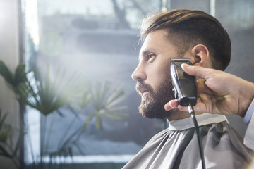 man having his beard trimmed