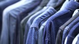Hand picking jeans shirts hanging in variation denim tone. Classic wear fashoin