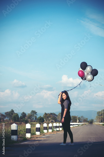 Poster An asian woman holding balloons while walking along the road with blue sky backg