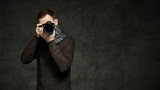 Young man photographing you at professional digital SLR camera, looking at result and gesturing thumb up over dark concrete wall background