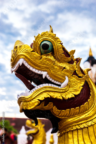 Poster Buddhism dragon guard statue in sunlight, Thailand. Religion