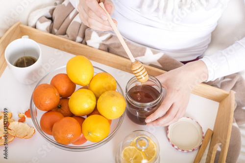 Poster Close up of hands with honey dipper in the air and citrus fruits served on wooden tray