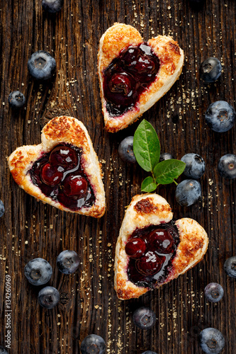 Poster Puff pastry cookies of heart shape filled with blueberries on wooden rustic back