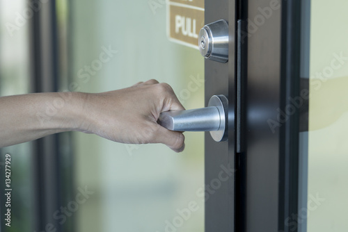 Poster hand hold handle of door, close up