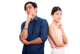 Studio shot of young Asian couple thinking together