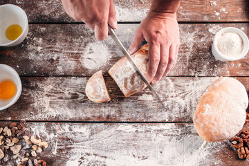 Cutting homemade bread on kitchen table flat lay. Top view on baker carving his fresh pastry on floured workplace with ingredients. Dinner preparing, new recipe degustation concept