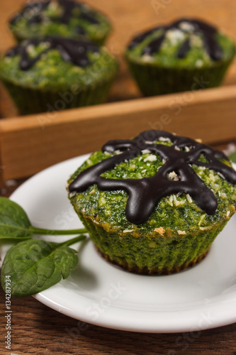 Poster Fresh muffins with spinach, desiccated coconut and chocolate glaze, delicious he