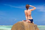 beautiful long haired woman in bikini relaxing on the rocks over the sea. Mahe Island, Seychelles