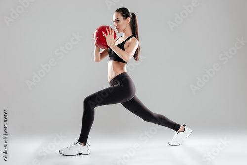 Valokuva Focused beautiful young sportswoman doing exercises with medicine ball