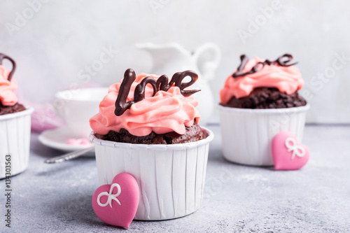 Poster Valentines and Mother Day, wedding greeting card with beautiful chocolate cupcake, pink cream and heart on gray stone background with copy space