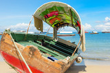 Wooden old boat sitting on the beach in Zanzibar on a perfect summer day under blue sky with calm sea. Many vessels are seen in the background extending to the horizon