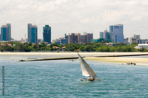 Staande foto Zanzibar Coastline of Dar Es Salaam. A fishing boat is sailing along the beach towards the huge drainage pipe extending in to the ocean. The skyline with skyscrapers is in the background