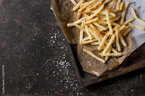Poster Fast food french fries potatoes with skin served with salt and herbs on baking paper on old rusty oven tray over dark texture background