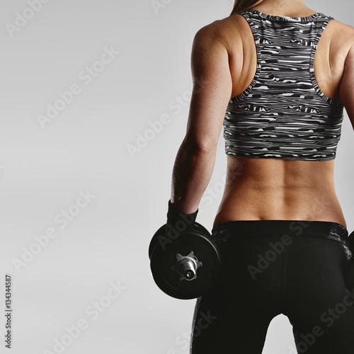 Silni sprawności fizycznej dziewczyny mienia dumbbells pozuje w studiu nad szarym tłem z kopii przestrzenią dla reklamy. Pojęcie sportu i szkolenia.