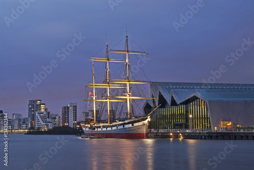Glasgow Riverside Museum and Tall Ship on river Clyde at night.