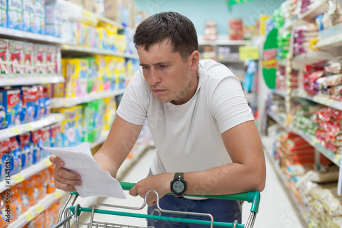 Man in supermarket is watching into list of necessary purchases. Shopping in grocery store