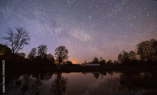 Night view of starry sky near small river.