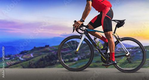 Mężczyzna na bicyklu na drodze między pięknymi górami