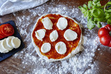 baking pizza rolled out dough with sauce and mozzarella