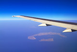 Aerial view of airplane wing and volcanic Santorini island in Greece