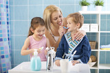 Mother and children brushing teeth. - 134402927