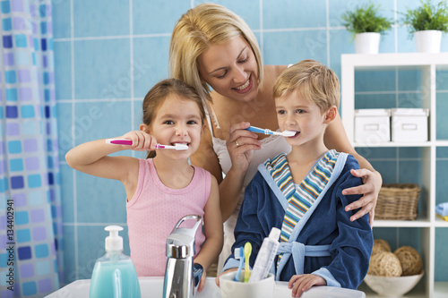 Mother and children brushing teeth. Poster