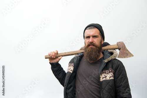 Poster bearded handsome serious man with rusty axe against cloudy sky