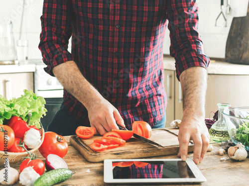 Man following recipe on tablet and cooking healthy food