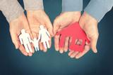 Familie und Haus aus Papier in den Händen halten - 134452194