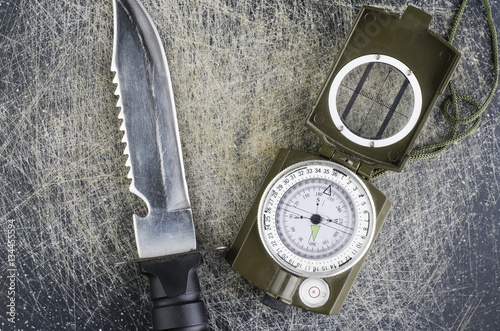 Survival Knife And Military Compass Close Up On Scratched Background Poster
