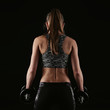 Постер, плакат: Close up of woman bodybuilder back over black background Fitness female standing with heavy dumbbells doing weightlifting exercise