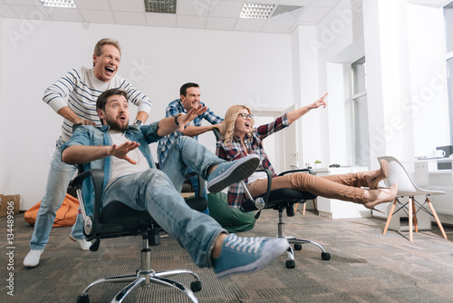 Joyful happy people sitting in the office chairs