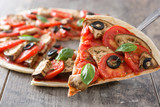 Showing vegetarian pizza slice with eggplant, tomato, black olives, oregano and basil - 134494746