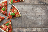 vegetarian pizza slice with eggplant, tomato, black olives, oregano and basil on wooden background.Top view - 134496564
