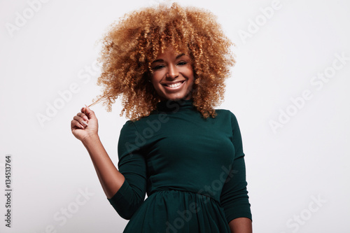 Poster smiling black woman have fun with her cyrly blonde hair