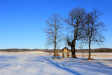 Kapliczka z ławeczką na pustkowiu w zimowym krajobrazie.