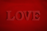 Wooden letters spelling LOVE on a red background