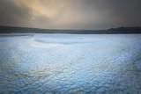 Frozen water reservoir on fields. Winter landscape.