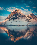 Antarctic landscape with snow covered mountains reflected in ocean water. Sunset warm light on the mountain peak, blue cloudy sky in the background. Beautiful nature landscape. Travel background.