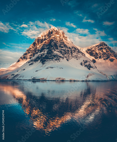 Fotobehang Antarctica Antarctic landscape with snow covered mountains reflected in ocean water. Sunset warm light on the mountain peak, blue cloudy sky in the background. Beautiful nature landscape. Travel background.