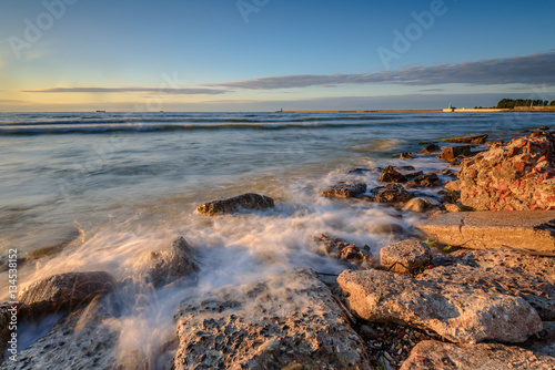 Blurred waves on the rocky beach. Baltic Sea at sunset light. Poland.