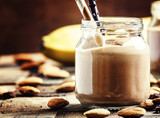 Banana-chocolate smoothie with almonds in glass jars, vintage wo