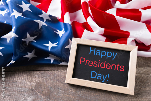 Poster the text happy presidents day written in a chalkboard and a flag of the United S