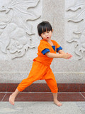 Kid girl in Shaolin monk orange clothes doing meditative tai chi exercise on Karate martial art sports training in chinese temple in thailand.
