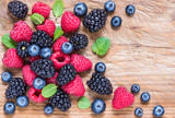 Berry fruits on wood background.