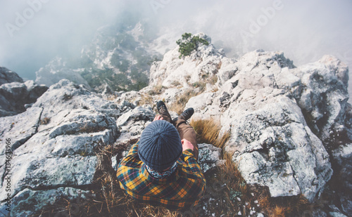 Traveler man relaxing alone on rocky mountain summit over clouds Travel Lifestyle success concept adventure active vacations outdoor top view