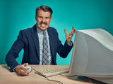 Angry businessman using a monitor against blue background