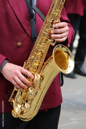 Poster player plays the saxophone in the brass band