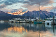Boats at a pier in Seward with mountains in background. Seward's Boat Harbor is situated on the northern edge of Resurrection Bay.